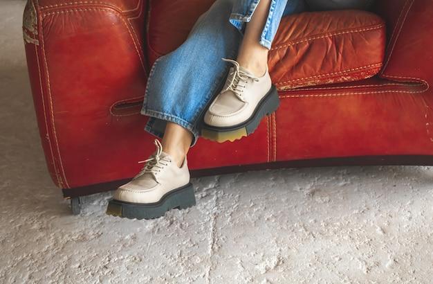 Красное кресло в стиле ретро и девочка-подросток в повседневной одежде, джинсах и кроссовках. мода и винтажное фото