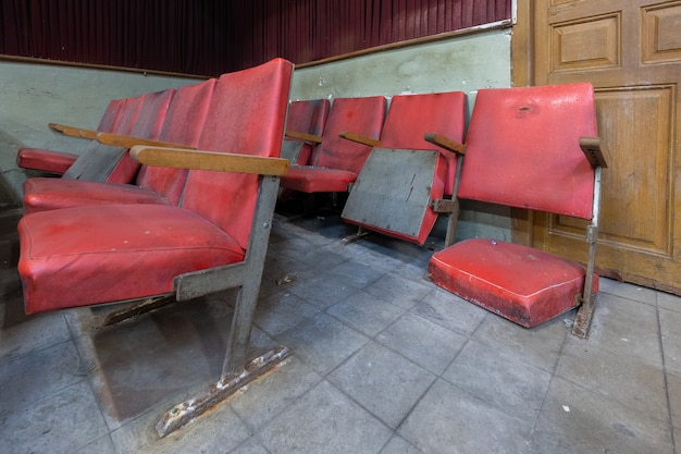 Red armchairs of an old abandoned cinema