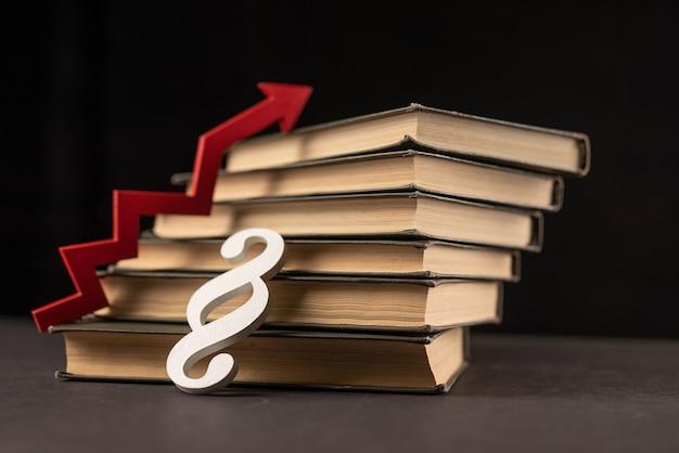 Красная стрелка, книги и знак параграфа. концепция инвестиций в образование и знания