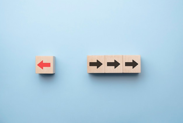Red arrow print screen on wooden block change direction from right to left which differ from black arrows