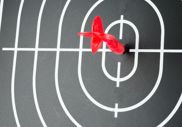 Red arrow shooting at center of black dart board