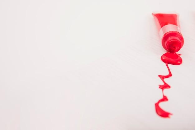 白い背景の上に絞った赤いアーティストカラーペイントチューブ