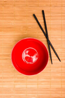 Red asian style bowl with chopsticks on textured placemat