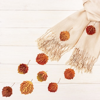 Red aspen leaves fly after beige scarf on light wooden background