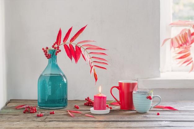 ガラスの花瓶とガマズミ属の果実の赤い紅葉と木製のテーブルの上のお茶