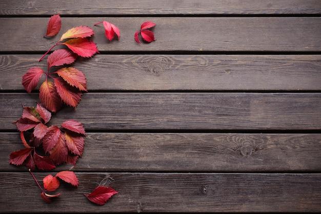 Красные осенние листья на старых деревянных фоне