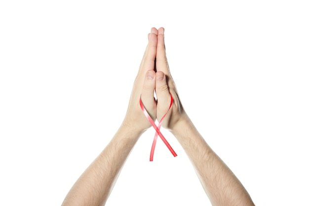 手に赤い意識リボン。 hivエイズ、薬物乱用または心臓病のシンボル。分離された白い背景。