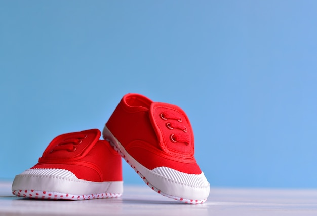 Red baby boy shoes on white wooden floor and blue background