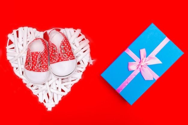Red baby shoes with white polka dots on a red background with gifts