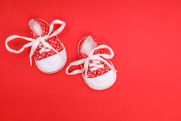 Red baby shoes with white polka dots on a red background