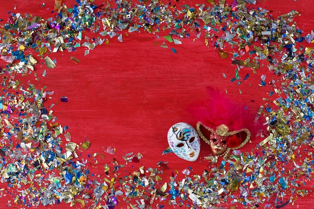 On a red background are two carnival masks and colored confetti around