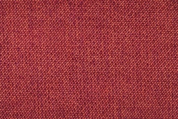 Red background from woolen texture textile, closeup. structure of the wicker fabric macro.