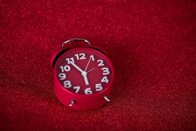 Красное фоновое изображение и красивый красный будильник концепция, время, дата