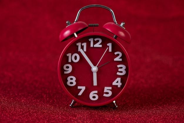 赤の背景画像と美しい赤い目覚まし時計のコンセプト、時間、日付