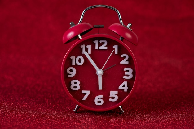 Red background image and beautiful red alarm clock concept, time, date