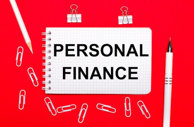 On a red background, a white pen, white paper clips, a white pencil and a notebook with the text personal finance. view from above