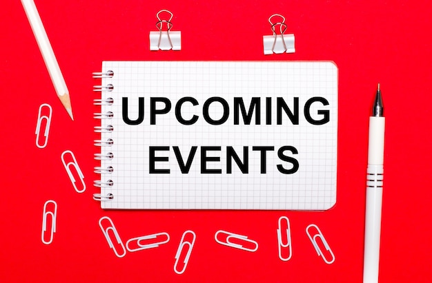 On a red background, a white pen, white paper clips, a white pencil and a notebook with the text ucoming events. view from above