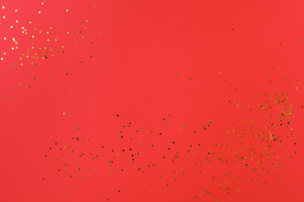Red background with golden candy stars. top view