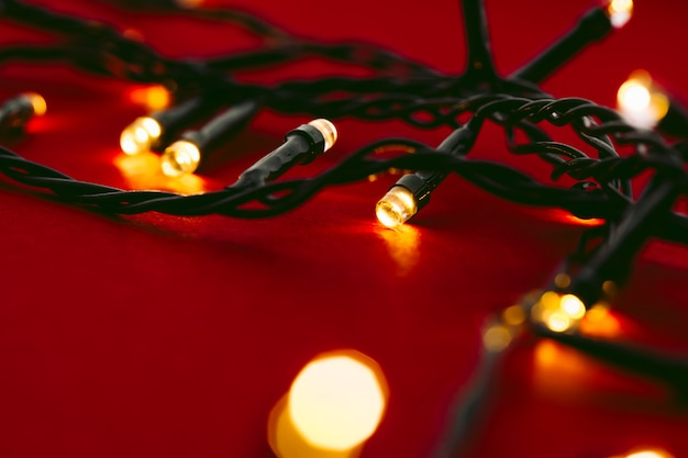 Red background with illuminated lights of garland
