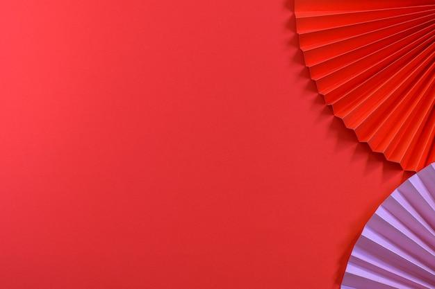 トレンディな環境に優しい赤とピンクの中国の扇子と赤い背景。グリーティングカード、パーティの招待状、その他のデザイン目的に最適なデザイン。
