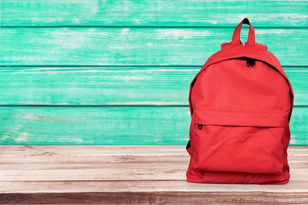 Красный рюкзак на деревянной поверхности с зеленой деревянной стеной на фоне, школьная концепция