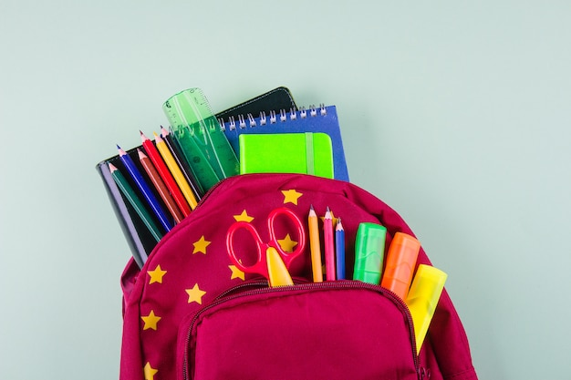 Red backpack with different colorful stationery on pastel green