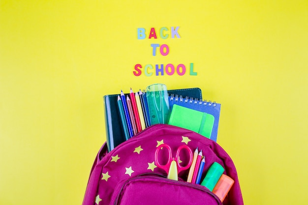 Red backpack with different colorful stationery on yellow