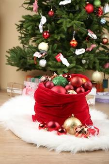 Красный мешок с елочными игрушками и подарками в номере