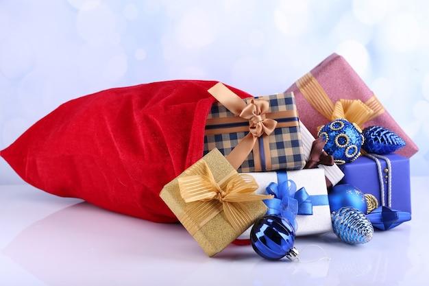 Красная сумка с елочными игрушками и подарками на ярком фоне