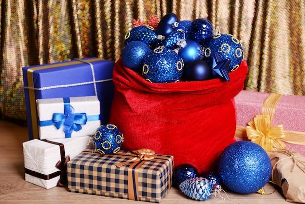 Красная сумка с елочными игрушками и подарками на тканевом фоне