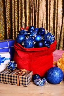 Красная сумка с елочными игрушками и подарками