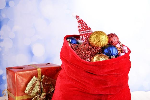 Красная сумка с елочными игрушками на ярком фоне