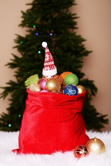 Красная сумка с елочными игрушками на фоне елки