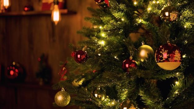 나무 벽 배경에 화환이 있는 크리스마스 트리에 있는 빨간 공