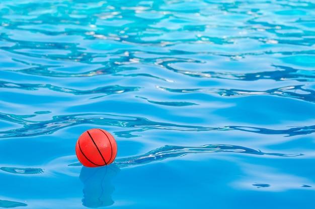 プールの青い水に赤いボール_