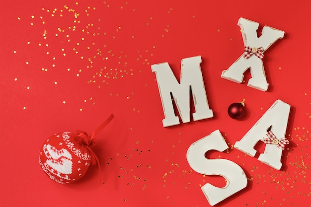 Red ball with a pattern for the christmas tree, big letters xmas with gold confetti and toys on a red background. top view
