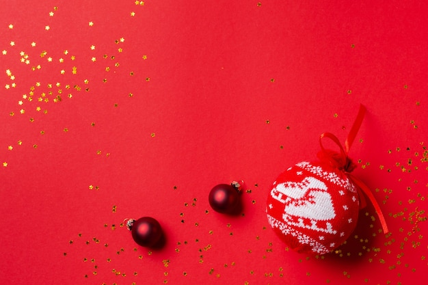 Red ball with pattern for the christmas tree with golden confetti and toys on a red background. top view