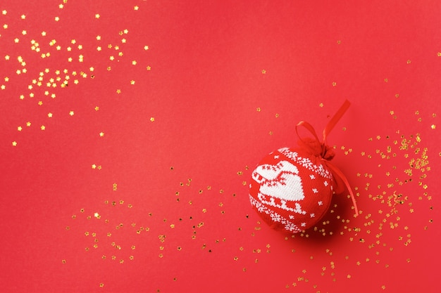 Red ball with pattern for the christmas tree with golden confetti and toys on a red. minimal christmas style and holiday concept.