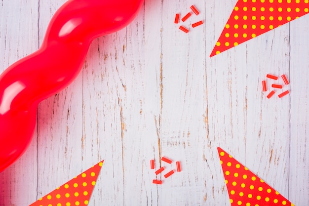 Red balloon, triangular paper and candies on wooden table