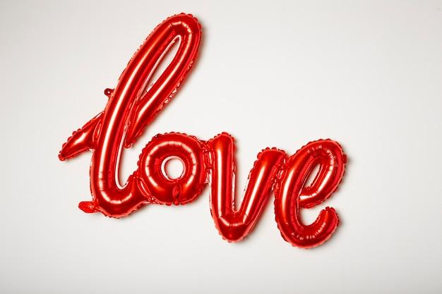 흰색 바탕에 알루미늄으로 만들어진 단어 사랑 빨간 풍선.