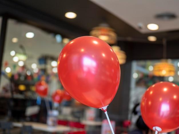 白いプラスチックの棒と背景をぼかす赤い風船