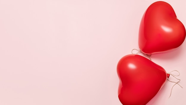 淡いピンクの背景にハートの形をした赤い風船。バレンタインデーのコンセプト。バナー、コピースペース