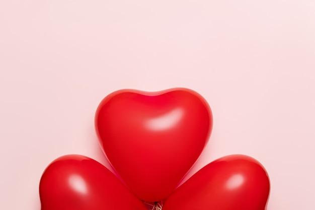淡いピンクの背景にハートの形をした赤い風船。バレンタインデーのコンセプト。