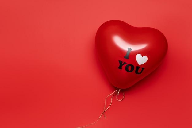 淡い赤の背景にハートの形をした赤い風船。バレンタインデーのコンセプト。