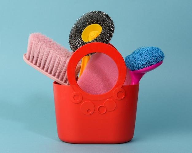 Красная корзина с губками для стирки, кисточки на синем фоне, набор