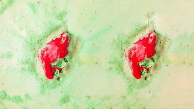 Red bathbomb dissolve in green bubble bath water