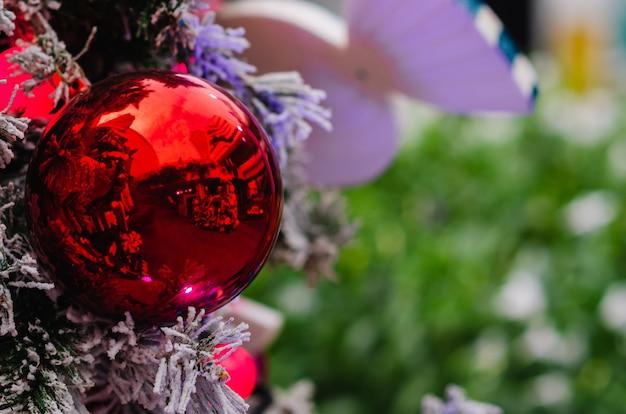 偽の雪が降るクリスマスツリーに飾られた赤い安物の宝石とライト