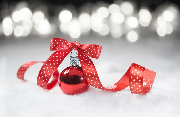 Red bauble with matching ribbon on snow
