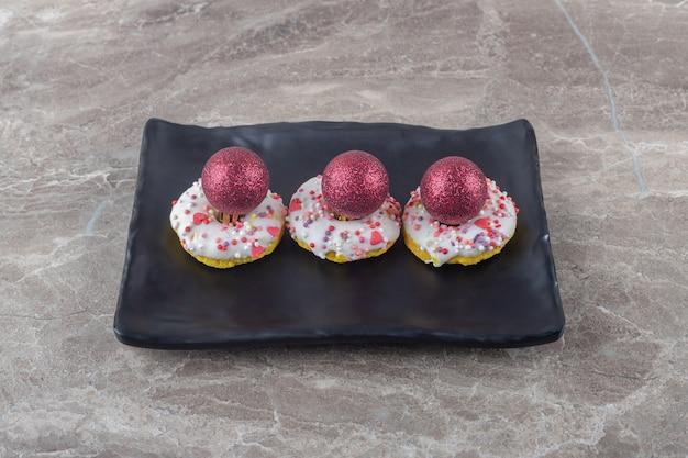 Красные безделушки сложены на маленькие пончики на черном блюде на мраморной поверхности