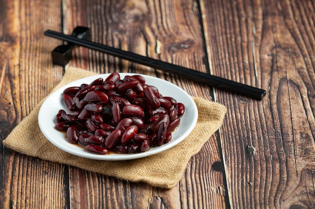 木の床の白い皿の場所で茹でた小豆